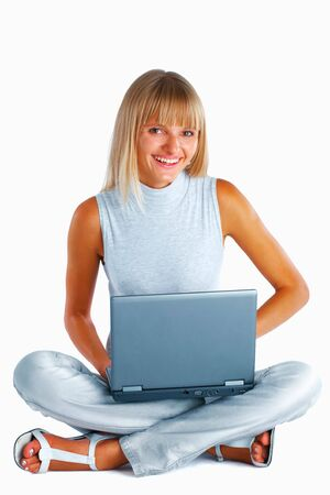 Smiling woman sitting with her legs crossed on the floor with laptop photo