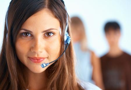 telephone headsets: Mujer hermosa joven con el kit manos libres port�til con algunas personas en el fondo Foto de archivo