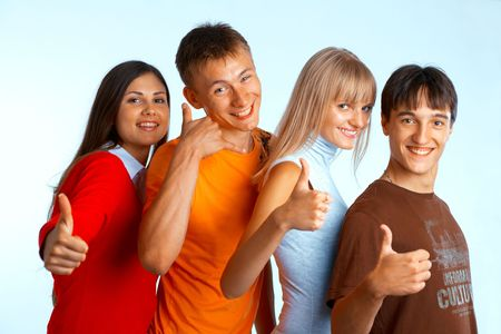 Four young people on white background laughing and giving the thumbs-up sign. Stock Photo - 5942561