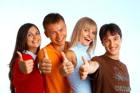 Four young people on white background laughing and giving the thumbs-up sign.  Stock Photo - 5942559