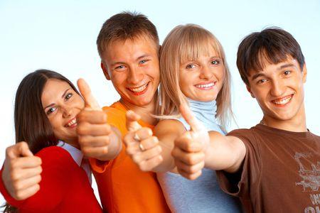 Quatre jeunes sur fond blanc contexte rire et donnant le signe de la cote.