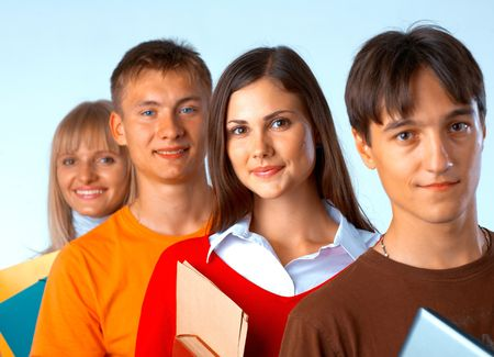 Casual group of college students smiling stand in a row with books on white  photo