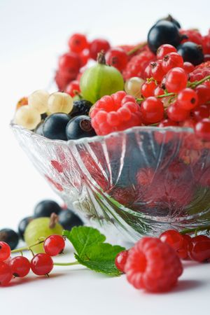 Mixed summer splitted berries in a cristal bowl on white photo