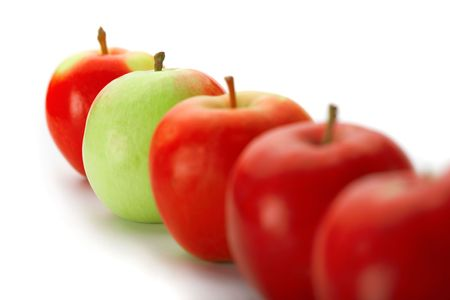 Group of red apples with one green one