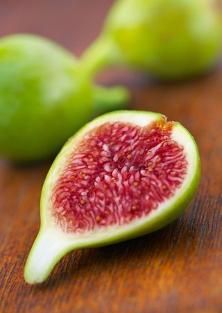 purple fig: Delicious vibrant honey sweet green fig. Figs halved Stock Photo