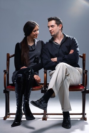 Young couple sitting on a theatrical bench looking at each other. photo