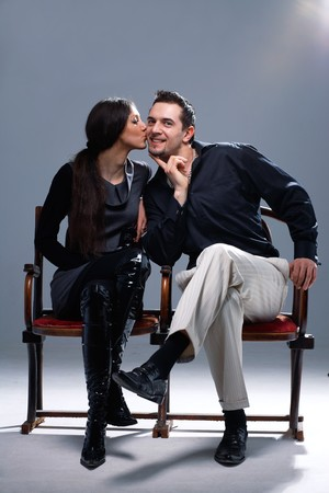 Young woman kissing a man in a cheek on the bench. photo