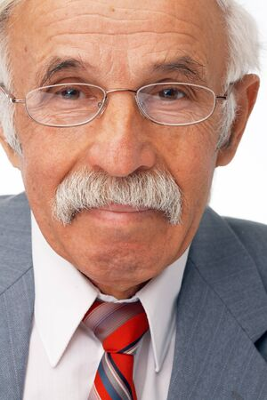 joyfull: Close-up portrait of an elder businessman looking at you and smiling.
