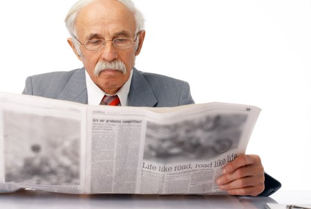 Elder man sitting and reading a newspaper over white.