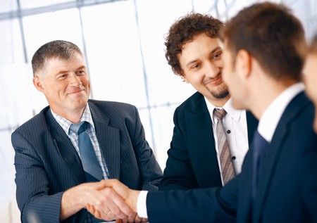 business deal: Business people shaking hands, coming to an agreement in the office. Stock Photo