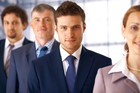 Young serious businessman standing in the row with his colleagues. photo