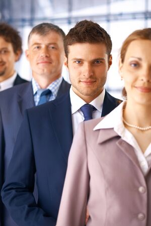 Closeup portrait of a young businessman standing in the row with his colleagues. photo