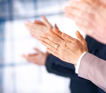 Colleagues applauding during a business meeting, focus on the hands.