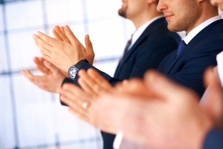applauding: Colleagues applauding during a business meeting, focus on the hands.