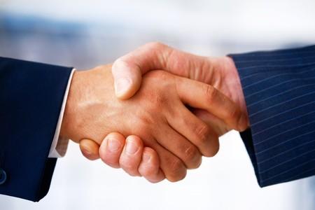 Closeup portrait d'hommes d'affaires se serrant la main, rendant un accord.