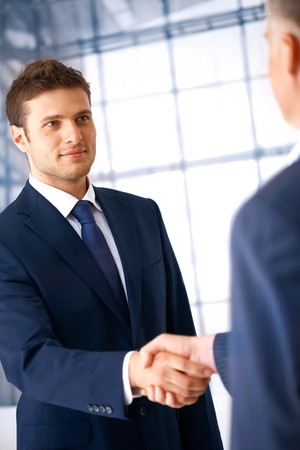 Business people shaking hands, coming to an agreement in the office. Stock Photo