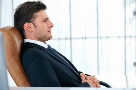 A young business manager is sitting relaxed in chair. Stock Photo