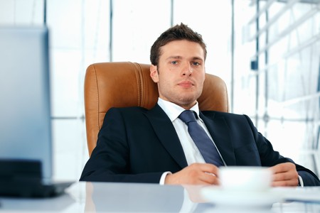 Young business executive sitting relaxed in chair looing at you. Stock Photo - 7225153