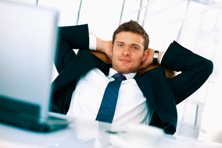 Young bussinessman sitting relaxed in his chair with hands under his head. photo