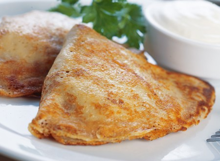 Close-up of two pancakes stuffed with meat on the plate with mayonnaise and parsley. photo