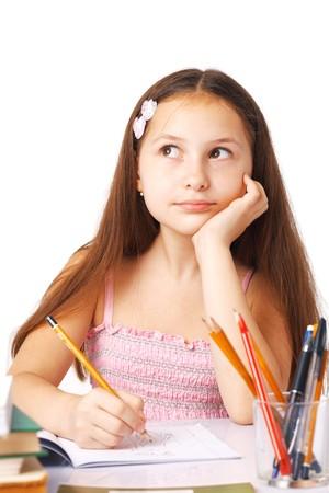 Cute little girl dessiner quelque chose, tenant sa main sous son menton, loin de la recherche.