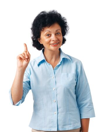 Portrait of a  happy senior woman pointing upwards on white.