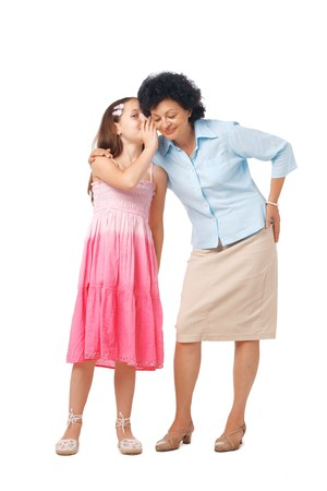 grand daughter: Grandmother and her grand daughter whispering something into her ear, full length. Stock Photo