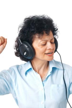 Active happy senior woman enjoying music over white background.