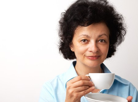 Close-up portrait of an elder smiling woman holding cup and saucer. photo