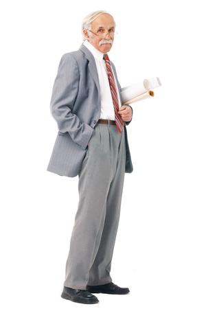 Full length portrait of an elder artist with paper rolls standing over white.