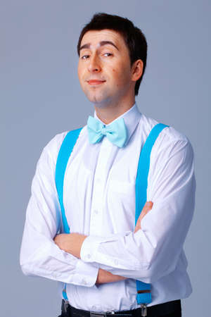 Man with blue bow tie and braces standing with his arms folded. photo