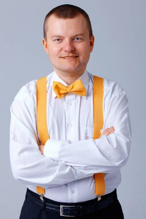 Man with yellow bow tie and braces standing with his arms folded.