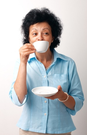 Portrait of an elder woman drinking from a cup and holding a saucer. photo