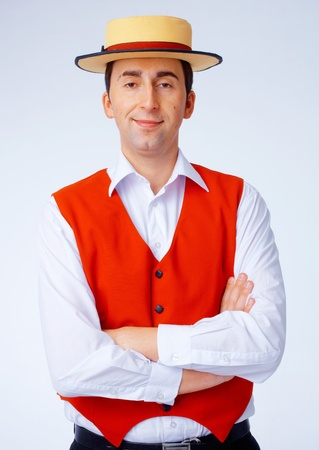 Man in yellow hat and red waistcoat standing with folded hands. photo