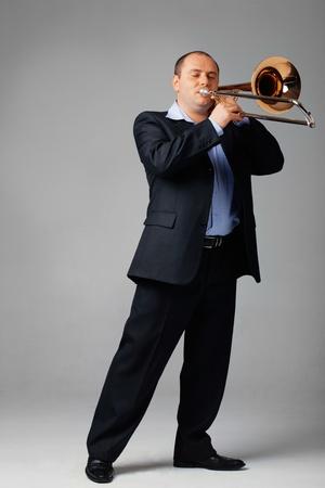 trombon: Retrato de un joven jugando su trombón.