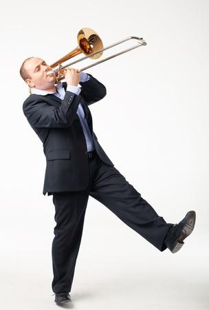 trombon: Retrato de un joven jugando su trombón en blanco Foto de archivo