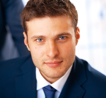 Closeup portrait of smiling young businessman working at the office. photo