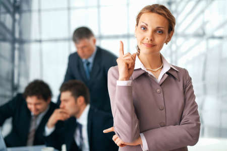 Portrait of a  happy businesswoman pointing upwards with her colleagues at the background. photo