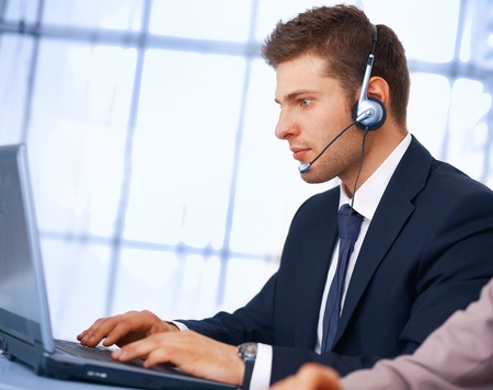 Closeup of a businessman with headset. He is working on laptop