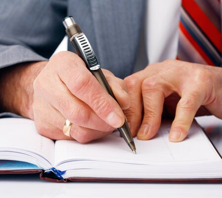 Close-up picture of businessman's hands writing in the dairy. Stock Photo - 9513992
