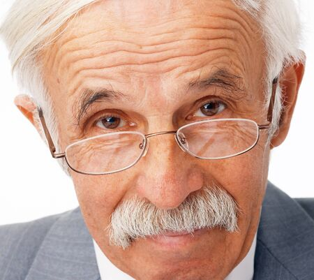 Close-up portrait of an elder businessman in the glasses looking at you.