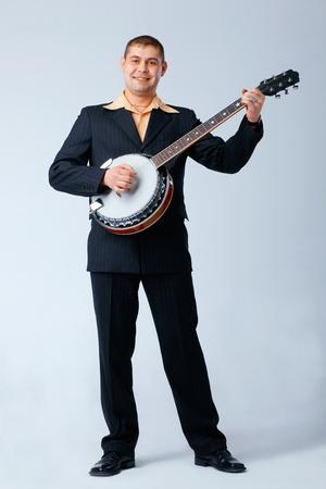 Homme de suite est permanent et jouer au banjo contre les blanche, pleine longueur. Banque d'images