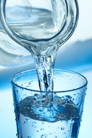 Water pouring from a jug into a glass on blue. Stock Photo