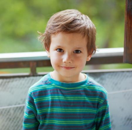 Retrato de un niño de pie y sonriendo a ti.