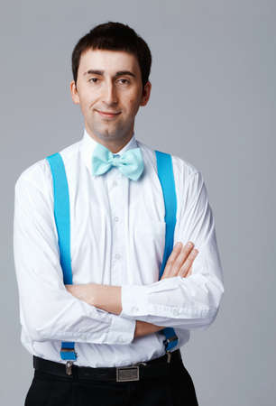 Man with blue bow tie and brases standing with his arms folded. Stock Photo - 14199761