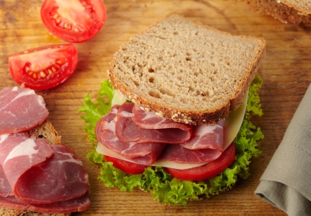 fresh sandwich with tomatoes, swiss cheese, lettuce photo