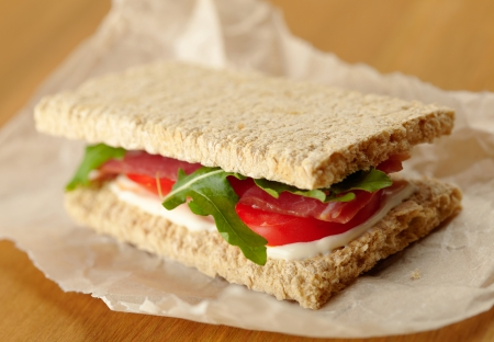 rukola: Homemade sandwich with bacon, tomato and  rukola on a pergament paper