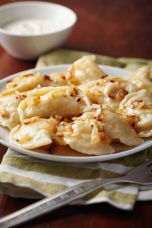 pierogi: Homemade Vareniki (dumplings) with potato and onion on a plate.