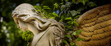 A fragment of ancient sculpture angel in a golden glow in the old cemetery. Symbol of love, invisible forces, purity, enlightenment, ministry. Chariot. Stock Photo
