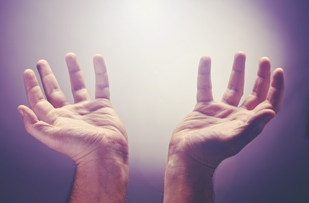 Hands raise with the palm opened up, worship or pray for good things under the light ray from heaven. Worship is an act of religious devotion usually directed towards a deity, god, angel Stock Photo